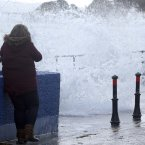 A woman avoids waves at the walkway at Whitehead in Antrim.<span class=