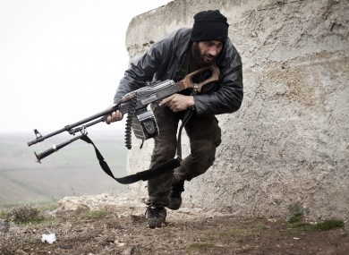 In this December 2012, file photo, a Free Syrian Army fighter takes cover during fighting with the Syrian Army in Azaz.