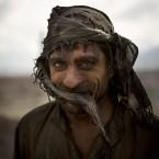 Afghan day laborer Zekrullah, 23, takes a break after preparing kilns to fire the bricks.<span class=
