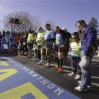 Mobility-impaired runners gather at the start line for a moment of silence before the 118th Boston Marathon.<span class=