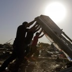 Workers flip a fallen wall as they search through destroyed homes.<span class=