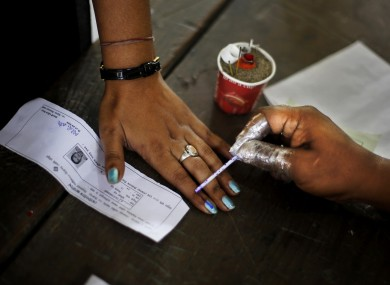 An election officer applies an indelible ink mark on the finger of a woman after voting Dibrugarh, in the northeastern state of Assam, India.