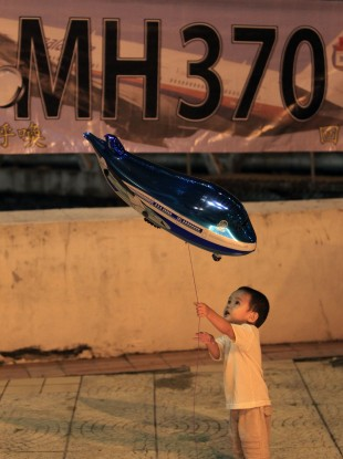 A boy plays with an aeroplane shaped foil balloon during a candlelight vigil for passengers aboard the missing Malaysia Airlines Flight MH370, in Kuala Lumpur.