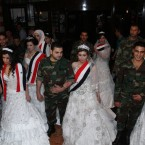 Couples take part in a mass wedding held at the Dama Rose hotel in Damascus, Syria. Twenty Syrian officers and soldiers wearing their military uniforms and brides wearing the national flag on their shoulders will get married during the event that was sponsored by the Founding Body for the Syrian Expatriates Association. Safaa Qara Mohammad, the chairwoman of the association said that the event was organized