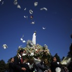 Worshippers throw flower petals to the statue of the Our Lady of Fatima at the Our Lady of Fatima shrine in central Portugal. <span class=