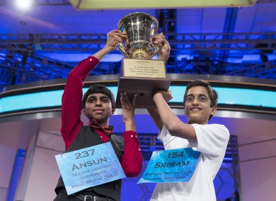 Ansun Sujoe, 13, of Fort Worth, Texas, left, and Sriram Hathwar, 14, of Painted Post, N.Y., raise the championship trophy after being named co-champions of the National Spelling Bee.