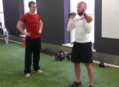 Ben tries out kettlebells with Ronan watching on.