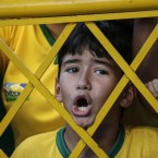 A young soccer fan shouts from outside the stadium fence asking to enter for Brazil's soccer team training session in Fortaleza.<span class=