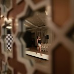An Indian model is reflected on a decorative mirror on the wall as she walks on ramp during an audition for the upcoming Lakme Fashion Week at a hotel in Mumbai, India.<span class=