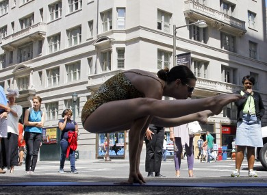 Thayne Dibble, an instructor with Bikram Yoga demonstrates yoga poses as people look on a corner of Rittenhouse Square.