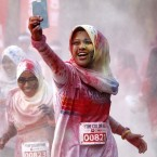 A participant takes a selfie as she runs through a