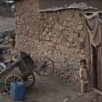 An Afghan refugee child, stands at the door way of his family's mud house, on the outskirts of Islamabad.<span class=