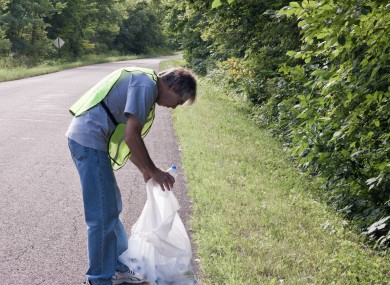 Man picking up litter on the side of the road.