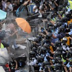 Riot police use pepper spray against protesters after thousands of people block a main road to the financial central district outside the government headquarters in Hong Kong. <span class=