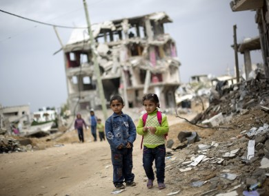 Palestinian school children walk through destroyed houses in Gaza City's Shijaiyah neighborhood last Sunday.