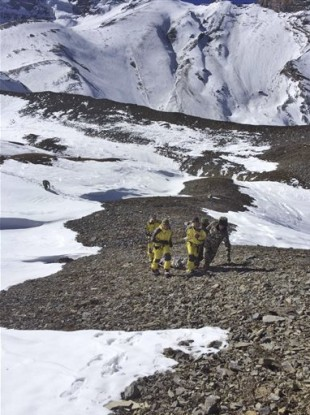 Rescue team members carry a victim of an avalanche before they airlift the body from Thorong La pass area in Nepal