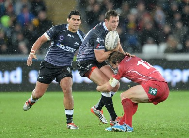 Ashley Beck carries the ball at a wet Liberty Stadium.