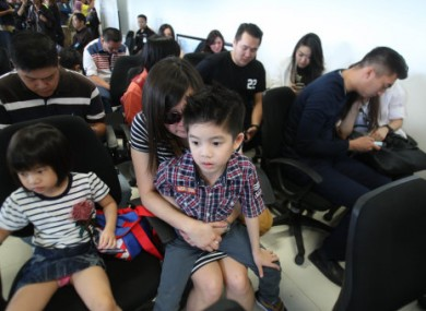 Relatives of the passengers of AirAsia flight QZ8501 wait for the latest news on the missing jetliner at a crisis center set up by local authority at Juanda International Airport in Indonesia
