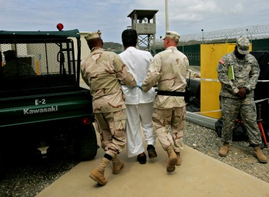 File photo of a Guantanamo detainee being escorted by US military personnel.