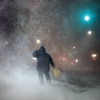A man battles fierce headwinds as he walks on Congress Street in Portland, Maine, during a blizzard.<span class=