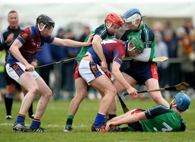 Kevin O'Brien (UL left, black helmet) and Kieran Bennett (LIT middle, blue and white helmet) pictured in action in the Fitzgibbon Cup today.