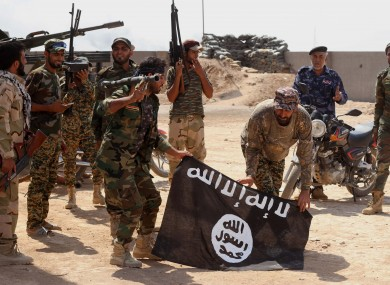 Iraqi forces holding the flag of the Islamic State group that they captured during an operation last year (File photo)
