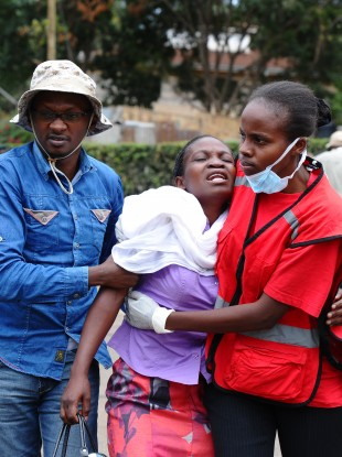 Kenya Red Cross staff help a woman after she viewed the body of a relative killed in yesterday's attack on a university