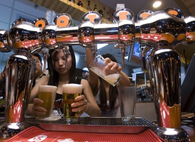 Waitresses fill beer glasses at the Beijing outlet for Hooters