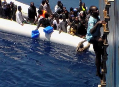 Migrants on a sinking rubber boat desperately being rescued in the Mediterranean Sea.