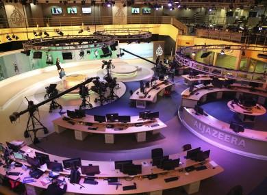 Staff members of Al-Jazeera International work at the news studio in Doha, Qatar