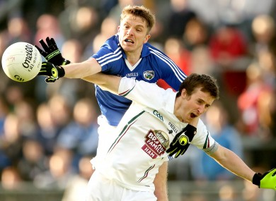 Ross Munnelly of Laois and Kildare's Ollie Lyons battle for possession.