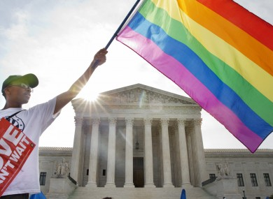 Carlos McKnight of Washington, waves a flag in support of gay marriage outside of the Supreme Court in Washington