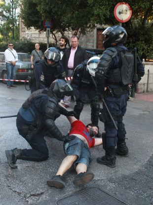 Riot police detains a demonstrator before a rally in Athens.