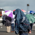 A punter gets caught in the rain on Day 2 of the Galway Races in Ballybrit.