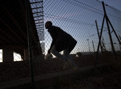 A migrant attempts to enter the Channel Tunnel at Calais in August