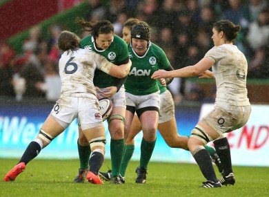 Paula Fitzpatrick is tackled by England's Hannah Gallagher.