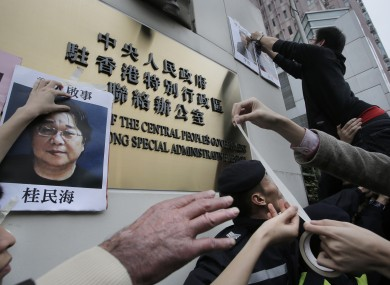 Protesters try to stick photos of missing booksellers during a protest outside the Liaison of the Central People's Government in Hong Kong