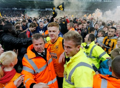 Hull's Sam Clucas gets escorted off the pitch after the final whistle.