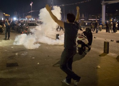 A man walks towards the teargas.