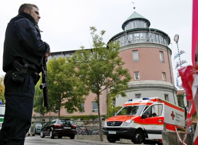 A police officer stands in front of Carolinum school in Ansbach, Germany.