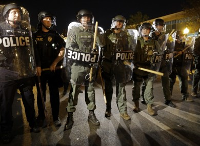 File: Police stand in formation as a curfew approaches in Baltimore in April 2015