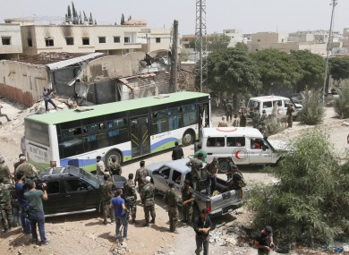Syrian government buses and Syrian Arab Red Crescent ambulances at the entrance of Darayya, southwest of Damascus.