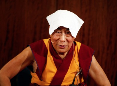 Tibetan spiritual leader the Dalai Lama wears a towel on his head to cool off during a press conference in Paris today.