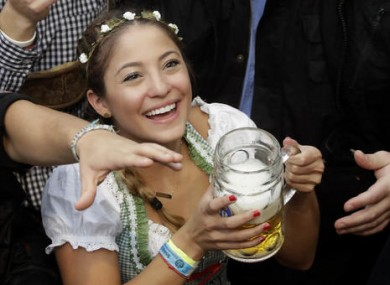 A young woman smiles with a beer during the opening of the 183rd Oktoberfest beer festival in Munich earlier today.