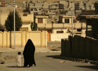 A woman and child walk in Mosul in 2009, before it was taken over by IS.