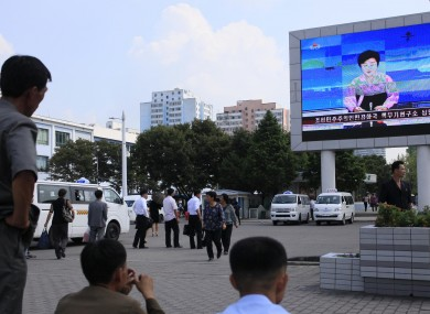 North Koreans watch a news report about the nuclear test on a large screen outside the Pyongyang Station.