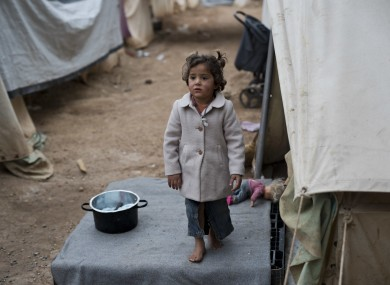 A child waits for her mother as she stands outside the family tent home at Ritsona refugee camp north of Athens.
