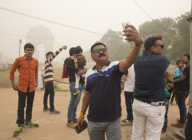 Indian tourists take selfies next to the war memorial India Gate in New Delhi earlier this month.