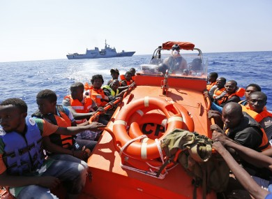 Migrants sit on a Norwegian Coast Guard boat after being transferred from the Italian Navy Ship Fulgosi during a migrant search and rescue mission off the Libyan coast.