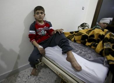 Syrian boys, evacuated from Aleppo, sit in a field hospital bed near Idlib, Syria.